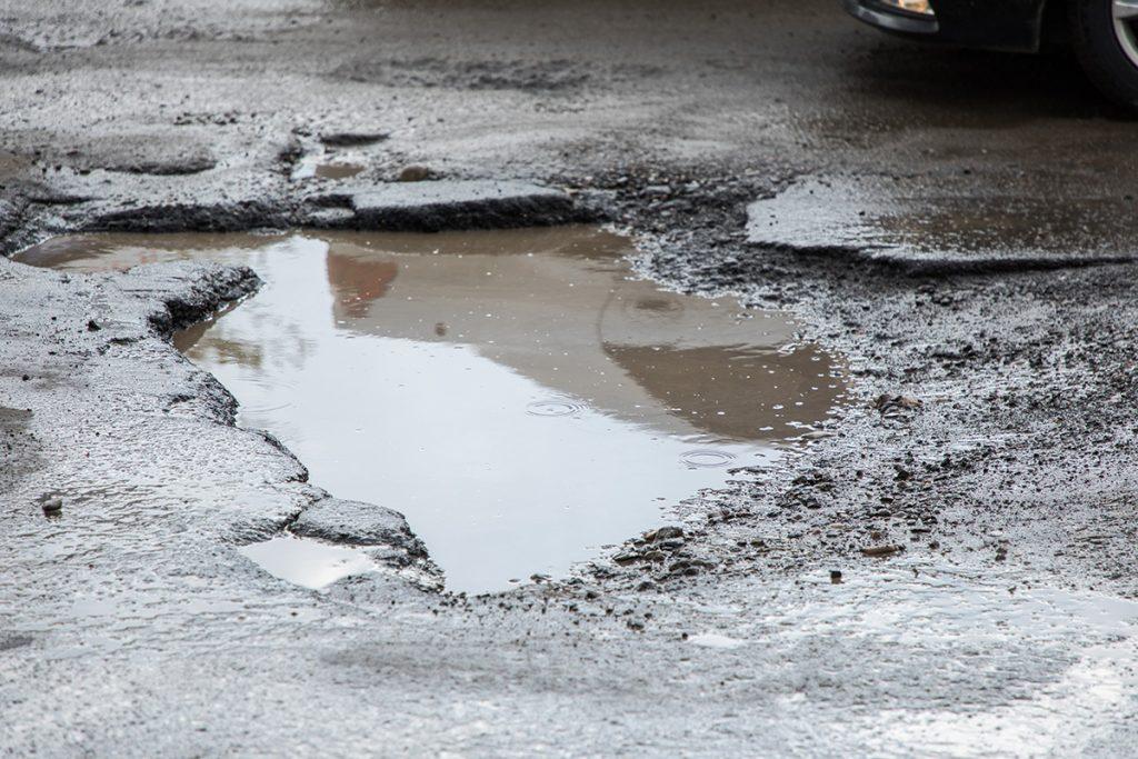 parking lot potholes, parking lot maintenance, pothole, pothole patchwork, asphalt maintenance